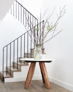 Entryway: decorative branches in glass vase on white marble-top table with wooden legs; solid timber floorboards and staircase; black metal balustrade: