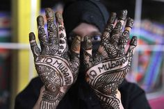 A Muslim woman decorates her hand with Henna in celebration of Eid