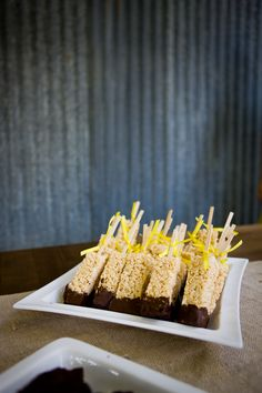 rice krispie treats, dipped in chocolate, on a stick, decorated with a yellow ribbon.
