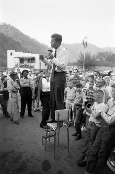 JFK'S 1960 CAMPAIGN: While part of every candidate's retinue, security was simply not the pressing, public concern in 1960 that it would suddenly and necessarily become within a few short years. Here, seemingly alone in a crowd in Logan County, West Virginia, JFK speaks from a kitchen chair as, mere feet away, a young boy absently plays with a jarringly realistic-looking toy gun.