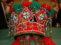 Norwegian bridal crown - embroidered cloth with yarn pompoms, beads and ribbons.