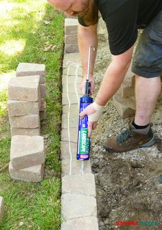 DIY Retaining Wall Construction for a Beautiful Garden - Jennifer Maker - Putting construction adhesive on bricks to make a retaining wall - Small Retaining Wall, Backyard Retaining Walls, Small Garden Retaining Wall, Retaining Wall Bricks, Retaining Wall Design, Retaining Wall With Steps, Retaining Wall Drainage, Building A Retaining Wall, Outdoor Landscaping