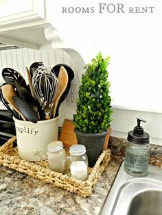 Kitchen: Basket platter with green element, salt and pepper shakers and napkin holder.