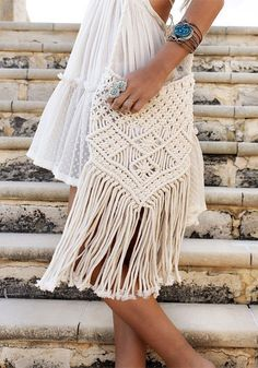 Go hands-free in style with this beige macrame fringe bag. It's made of cotton blend and features cutout crochet design together with fringe trim at bottom. | Lookbook Store