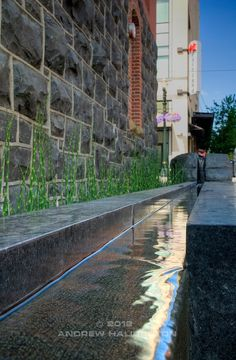Vera Katz Sidewalk Park, or Sliver Park. Includes a bioswale for stormwater treatment and a water channel of sculpted black basalt, part of the building's storm water management, fed by roof runoff.  Design by Scott Murase of Murase Associates.