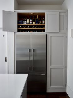 Clever wine storage above a fridge freezer by Higham Furniture A storage cupboard above an American style fridge freezer is a great place to store wine and other bottles as seen here in this Handleless Shaker kitchen in Wimbledon. Open Plan Kitchen Living Room, Kitchen Dining Living, New Kitchen, Country Kitchen, Shaker Style Kitchens, Home Kitchens, Shaker Kitchen, Kitchen Furniture, Kitchen Interior