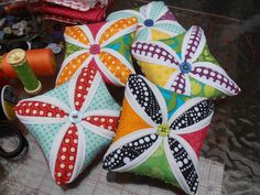 Pincushion Tutorial - - that red and aqua one looks beautiful. I wonder what a cathedral window with the prints/plain fabric reversed looks like?