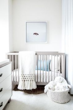 White and gray nursery features a gray crib, Oeuf Sparrow Crib, lined with organic cotton bedding as well as a blue pillow alongside a white cowhide rug atop a parquet wood floor. Basket of bunny rabbits to complete the soft look.