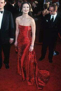 CATHERINE ZETA-JONES  The Welsh beauty shone at the 1999 Oscars in a sparkling fiery red Versace gown. The matching rouge lips and luscious dark tresses were the ideal finishing touches. (1999)