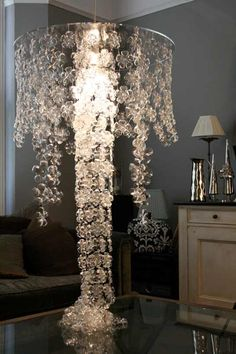 Plastic bottle  chandelier. I LOVE how this pools onto the surface below. Tres Chic!