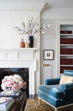 Sophisticated living room features a white fireplace mantle accented with a glossy black surround next to a blue velvet roll arm reading chair illuminated by a brass floor lamp placed in front of a built-in bookcase.Designed by Christopher Burns