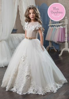 This cap sleeved San Francisco dress is an elegant flower girl dress, featuring voluminous tulle skirt and 3D flower accents scattered all over the gown. Topped with a jewel neckline and an open back, the bodice is drenched in flowers with a bow sash defining the natural waistline. Long, richly gathered skirt with a scalloped lace hem flows into a beautiful short train.