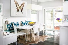 Contemporary breakfast nook is filled with a built in dining bench lined with peacock blue pillows under  a framed butterfly print facing a white lacquered dining table lined with whiye modern dining chairs atop a brown cowhide rug illuminated by a rectangular linen chandelier.