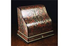 A Fine Late 19th Century Boulle-work Stationary Cabinet with maker's label 'J F Renner, 16 Castle St London'. The piece intricately decorated with scrolling brass inlaid on a red tortoiseshell ground and having a sweeping slope front with two doors opening to reveal stepped rosewood letter racks, with watch, postage stamp and match compartments to the back, and a partitioned drawer below, 13¾ in