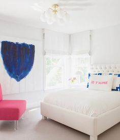 Stylish white kid's room with pink and blue accents is furnished with a white tufted headboard supporting a white bed complemented with white hotel bedding topped with a white and pink pillow placed in front of blue greek key pillows.