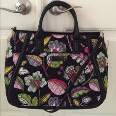 Vera Bradley Moon Blooms Trapeze Tote Functional tote featuring two handles and a removable faux-leather shoulder strap. There is one slip pocket on the front of the bag with one zippered and three slip pockets on the interior. Faux-leather trim around the bag and the bottom has grommets to protect it from getting dirty. Vera Bradley Bags Totes