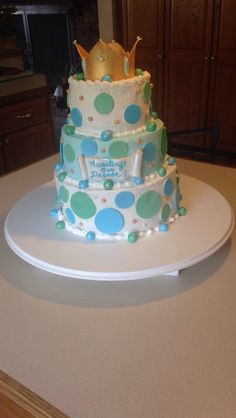 Awaiting Our Prince baby shower cake. Tiered with vanilla and chocolate cakes filled with chocolate chip cream centers. Iced in buttercream. Crown polka dots balls and scroll out of fondant with pearl accents.