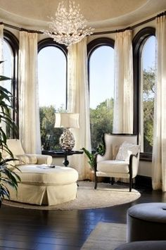 tastefully white room, gorgeous black arched window frames and subtle window treatments
