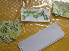 Children cutting out leaves from wallpaper and creating caterpillars with sponge covered cotton reel. Great for counting and saying how many altogether (Cardinal Principle)