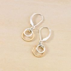 """Two hand hammered circles hang from leverback earwires, the largest measuring about 3/8"""". The inner circle on these is sterling silver, and the larger circle is gold filled."""