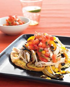 These mile-high healthy tostadas made with shredded chicken sport a big helping of corn, peppers, and onions, plus salsa.