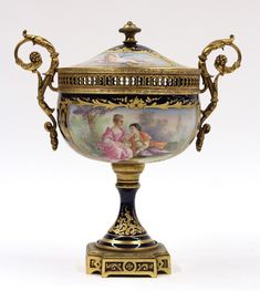 *Sevres porcelain gilt metal mounted urn, the removable domed lid above a bulbous body decorated with a cartouche to each side depicting a rural scene and a courting couple, flanked by scrolled foliage handles above a waisted standard on a footed gilt base, marked overglaze S, underglaze red Chateau de Versailles Manufacture Française. 19th century