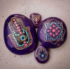"""Hand painted rocks - """"Good Luck"""" decorative pieces are result of mixing few several cultures. The Jewish/Arabic Hamsa is combined with Indian Mandala and drawn dot paintings - the style of Australian aboriginal art. The Hamsa hand is symbolize the five books of the Torah, bring happiness to the holder and protect the owner from the evil eye. A mandala is a spiritual and ritual symbol in Hinduism and Buddhism, representing the universe and welcomed Wisdom and Prosperity."""