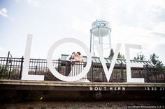 photo of bride and groom in 'LOVE' sign in Virginia, couple kissing in opening of the sign