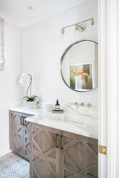 A polished nickel 3-light sconce is mounted above a silver convex mirror hung from a white wall over a brown oak washstand.