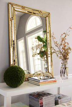 hallway leaning gold mirror stacked magazines white lacquer console table