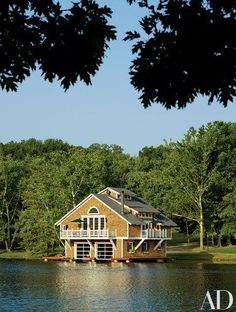 """Moore and the clients decided on the Shingle Style after researching boathouses from around the country. """"It just felt right for the wooded setting,"""" he says. """"It's a beautiful piece of property. You wouldn't know you're in the confines of a pretty good-size metropolitan area.""""   archdigest.com #boatonlakesummer"""