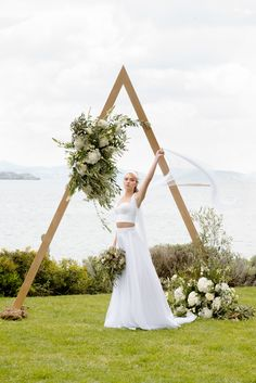 Triangle wedding arches for Boho weddings in Greece.  Most of triangle wedding arches are boho ones, so if you are planning a boho wedding its our suggetion to consider a triangle.  To make your triangle arch boho chic, choose a wooden or a metal arch and decorate it with blooms that you've chosen the wedding decor, pampas grass, feathers and lots of greenery and foliage.  #weddingarch #trianglearch #weddingingreece #weddingdecoration #weddingceremony #weddingplannergreece