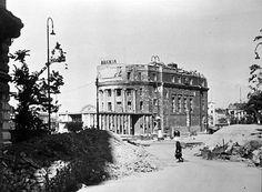 """""""Trümmerfrau"""" mit Rucksack vor der durch Bomben zerstörten Urania in Wien. Nach Beendigung des Krieges sind Lebensmittel und Brennmaterial rar und viele Menschen versuchen in den zerstörten Häusern das nötige Brennmaterial zu organisieren."""