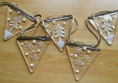 This is beautiful fused glass bunting, handcut by me and fused in my kiln. The snow flakes and Christmas trees have been kiln carved and you can feel the indent that creates the design in the back of the bunting. These would look stunning in any Christmas window with twinkly lights