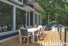 Modern outdoor dining and living spaces on the deck of a Muskoka cottage in shades of white, beige, and blue.