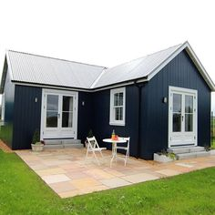 Gorgeous, simple, family style cottage home with blue exterior paint. One Bedroom Wee House Patio by The Wee House Company