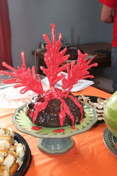 Volcano cake. Chocolate bunt cake (I used a rose pan), with chocolate glaze as the base.  I plugged the hole in the top with a marshmallow.  To make the erupting lava I put wood skewers on waxed paper and filled a baggie with melted red candy melts, snipped the corner off and piped it over the skewers.  The rest of the red I drizzled over the sides to make lava flows and made a big blob of it over the marshmallow. Right before the party, I stuck the skewers in the cake.