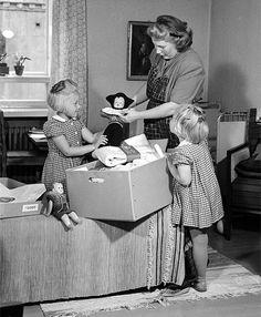 Äiti lapsineen katselemassa äitiyspakkauksen sisältöä 1950-luvulla.