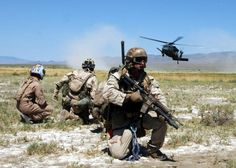 050713-N-9500T-250 Fallon, Nev. (July 13, 2005) -- Pararescuemen and survivors prepare to board an HH-60G Pavehawk helicopter during a training scenario as part of Desert Rescue. Desert Rescue is a multi-service, multi-national training exercise held annually to prepare combat search and rescue teams to extract downed personnel in a variety of environments and situations. U.S. Navy Photo By Photographer's Mate Second Class (AW/NAC) Scott Taylor (RELEASED).