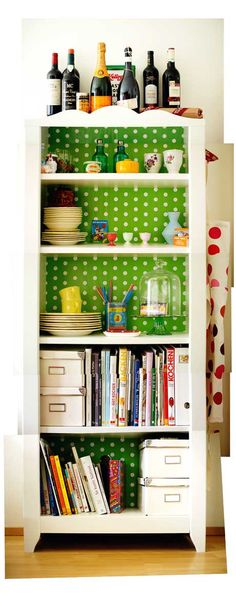 With the back lined in bright patterned paper, it serves as practical and attractive storage for cookbooks, plates and knickacks: