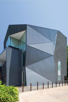 Contemporary residence's facade black stucco concrete with a matched metal folding wall and roof - CAANdesign