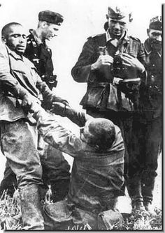 German soldiers look on with amusement as a Russian soldier tries to help his badly wounded comrade.