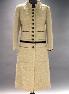 Chanel White Wool Boucle Ensemble   French, 1960s   Comprising a dress with black taffeta sleeveless bodice and slim wool skirt and a coat with slit pockets stacked three high on each side, black taffeta insets on sleeves, quilted lining, leather belt, and black leather buttons with Chanel logo, buttons repeated on skirt