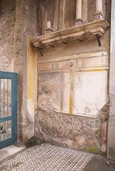 House of the Faun - The fauces is decorated in the first style to a height of about 2.5 metres. Above this on either side is a tufa shelf on which rests a lararium consisting of a temple facade with small Corinthian columns.