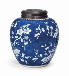 A CHINESE BLUE AND WHITE OVOID JAR KANGXI PERIOD (1662-1722) Decorated with alternating of prunus on a cobalt blue cracked-ice ground 9? in. (24.4 cm.) high, wood cover