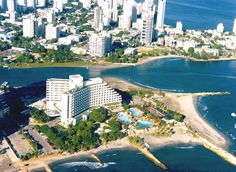 """El Laguito"", in Cartagena is the far end of the peninsula of Bocagrande. This here is the Hilton Hotel and the open sea is the Caribbean (the lower edge of the photo); the water behind the hotel on the left is an open lagoon and the bay is in the upper right side. That land is called ""Bocagrande."""