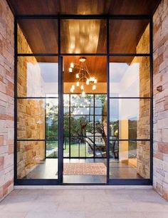 i like how the entry porch stone walls continue right through the glass wall, and the ceiling does the same