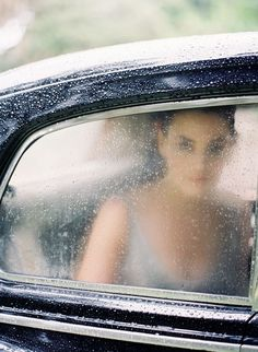 Lovely rainy day wedding photo from inside of a car.