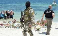 A Tunisian special force officer and a policeman patrol the beach as tourists take part in a memorial ceremony on July 3, 2015, at the resort of Port el Kantaoui/AFP
