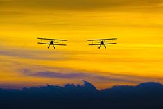 photo by Moose Peterson of two biplanes in flight for article on photographing airshows